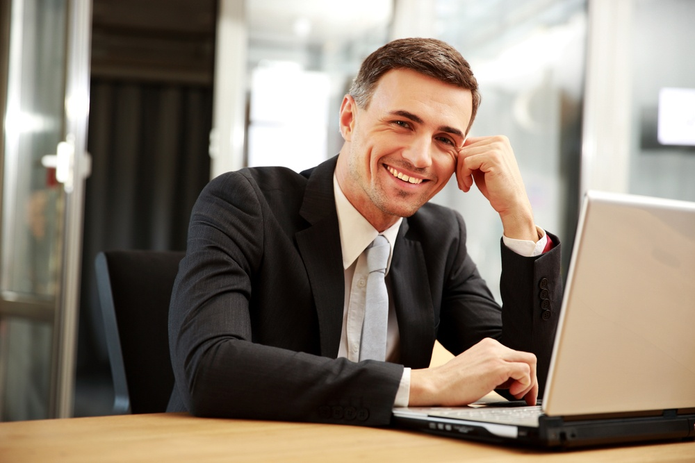 Smiling businessman sitting with laptop at office.jpeg